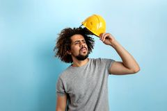 Курчав-головый красивый человек нося серую футболку стоит со шлемом безопасности выглядя кос со сконцентрированное стоковая фотография rf