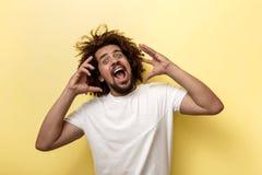 Курчав-головый человек брюнета кричащ и держащ его оружия около стороны Яркие эмоции над желтой предпосылкой стоковые фотографии rf
