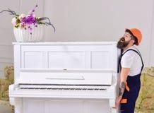 Курьер поставляет мебель, двигает вне, перестановка Человек с работником бороды в шлеме и прозодеждах поднимается вверх, усилия д стоковое фото