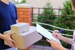 Курьер человека приносит заказ к клиенту, дает ручку и бумагу к Sig стоковое фото rf