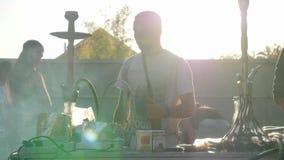 Куря мужчина с кальяном испускает толстый помох от рта дальше под открытым небом в лучах солнца видеоматериал