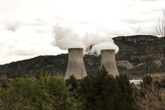 Куря печные трубы в атомной электростанции между горами стоковое изображение