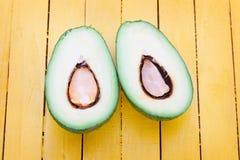 2 куска авокадоа на желтой деревянной таблице планок Стоковая Фотография
