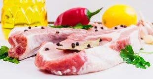 2 куска говядины стейка, зеленых цветов, чеснока, лимона, красного перца и подсолнечного масла или оливкового масла, и лист залив Стоковые Изображения RF