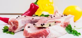 2 куска говядины стейка, зеленых цветов, чеснока, лимона, красного перца и подсолнечного масла или оливкового масла, и лист залив Стоковое Фото