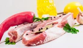 2 куска говядины стейка, зеленых цветов, чеснока, лимона, красного перца и подсолнечного масла или оливкового масла, и лист залив Стоковая Фотография RF