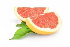 2 куска грейпфрута на белой предпосылке с зелеными листьями Стоковое Изображение