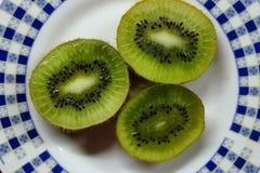 3 куска кивиа на белой и голубой плите еда принципиальной схемы здоровая плодоовощ тропический Стоковые Изображения RF