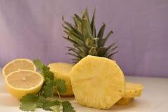 Куски ананаса лимон и петрушка на белой таблице Стоковые Фотографии RF