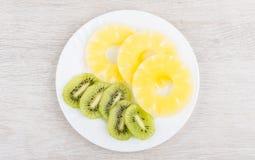Куски ананаса и кивиа в белой плите Стоковая Фотография