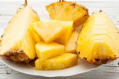 Куски ананаса на белой деревянной предпосылке Стоковая Фотография