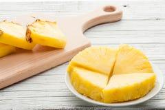 Куски ананаса на белой деревянной предпосылке Стоковое фото RF