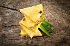 Куски ананаса на деревянной предпосылке Стоковые Изображения