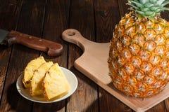 Куски ананаса на темной деревянной предпосылке Стоковые Изображения