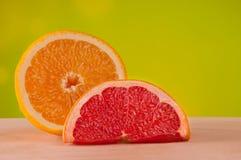 Куски апельсина и грейпфрута на деревянной доске с желтой предпосылкой Стоковые Изображения RF
