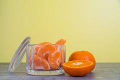 Куски апельсина мандарина в стеклянном опарнике с ярким желтым backg Стоковое фото RF