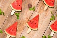 Куски арбуза на ручках Popsicle арбуза на деревянной белизне Стоковое Изображение RF