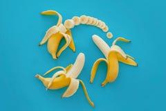 Куски банана на яркой голубой бумаге, квартире ультрамодного плодоовощ современной Стоковое Изображение