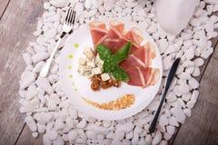 Куски ветчины, грецких орехов и сыра на плите Нож и вилка около блюда на белизне облицовывают предпосылку роскошный обедающий Стоковые Изображения
