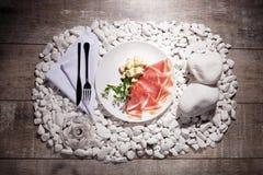 Куски ветчины и сыра на белой плите Бокал вина и блюдо на белизне облицовывают предпосылку Дорогой обедающий Стоковое Изображение RF