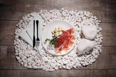 Куски ветчины и сыра на белой плите Бокал вина и блюдо на белизне облицовывают предпосылку Дорогой обедающий Стоковые Фото