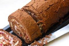 Куски вкусных крена и ножа торта губки шоколада Стоковые Фотографии RF