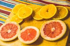 Куски грейпфрута и апельсина на деревянной разделочной доске фотографируют Стоковое фото RF