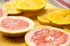Куски грейпфрута и апельсина на деревянной разделочной доске фотографируют Стоковые Изображения