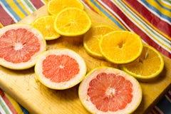 Куски грейпфрута и апельсина на деревянной разделочной доске фотографируют Стоковые Фото