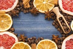 Куски грейпфрута и лимона, кофейные зерна, циннамон, анисовка звезды и деревянная ложка на голубой деревянной предпосылке Стоковое Изображение