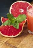 Куски грейпфрута и стекло сока на таблице Стоковое Изображение RF