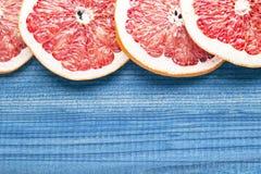 Куски грейпфрута на голубой деревянной предпосылке Стоковое фото RF