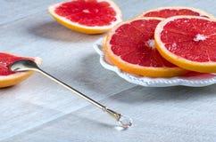 Куски грейпфрута на плите и ложке Стоковые Фотографии RF