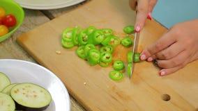 Куски женщины зеленеют длинный перец chili с ножом на деревянной доске акции видеоматериалы