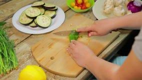 Куски женщины зеленеют длинный перец chili с ножом на деревянной доске r видеоматериал