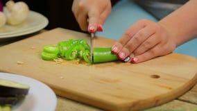 Куски женщины зеленеют длинный перец chili с ножом на деревянной доске r сток-видео