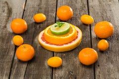 Куски и tangerines цитрусовых фруктов на деревянном столе Стоковое Изображение