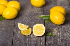 Куски лимона лежат на деревянной поверхности, далеких больших желтых лимонах Стоковое Изображение RF