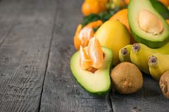 Куски мандарина внутри половинного авокадоа и другого тропического плодоовощ на деревянном столе Стоковая Фотография