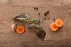 Куски моркови, листьев базилика, гвоздичного дерева чеснока и черного подбадривающего Стоковая Фотография RF