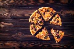 Куски домодельной пиццы на картоне с базиликом на деревянной предпосылке Взгляд сверху Конец-вверх Стоковая Фотография RF