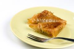 Куски пирога бахлавы с грецкими орехами служили на плите над белой предпосылкой Стоковые Фотографии RF