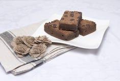 Куски пирожного шоколада на белой плите Стоковые Фотографии RF