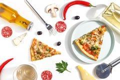 Куски пиццы, ингредиентов и столового прибора на белой предпосылке Взгляд сверху стоковое фото