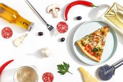 Куски пиццы, ингредиентов и столового прибора на белой предпосылке Взгляд сверху стоковые фото