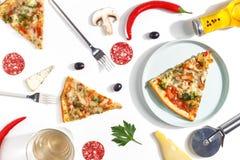 Куски пиццы, ингредиентов и столового прибора на белой предпосылке Взгляд сверху стоковое изображение rf