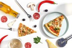 Куски пиццы, ингредиентов и столового прибора на белой предпосылке Взгляд сверху стоковая фотография rf