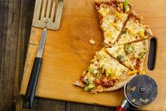 Куски пиццы на деревянной доске на темной таблице, сверху стоковые изображения