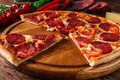 Куски пиццы на деревянном диске Высококалорийная вредная пища, тучная стоковая фотография
