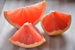Куски розового грейпфрута на деревянной доске Стоковое Изображение RF